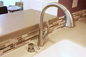 Close-up of countertop with raised bar, tile backsplash & undermount sink with brushed nickel faucet