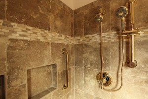 Master shower with porcelain tile and brass finishes